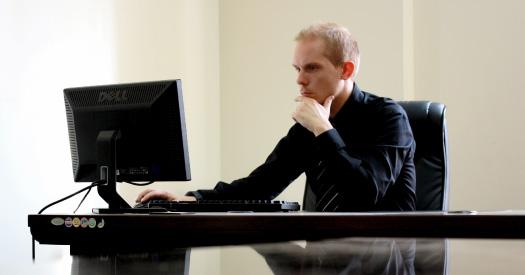 man sitting at desk thinking