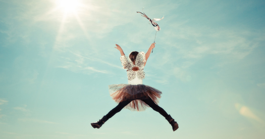girl dressed up as a fairy, jumping high in the air