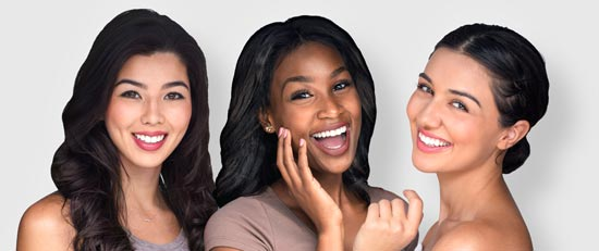 multicultural group of three woman laughing and smiling showing white teeth